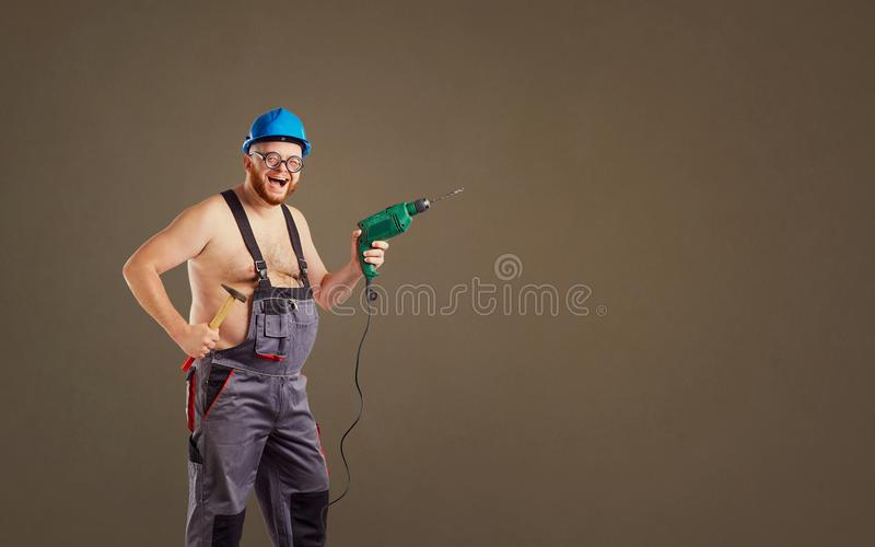 Gruby śmieszny mężczyzna budowniczy z świderem fotografia stock