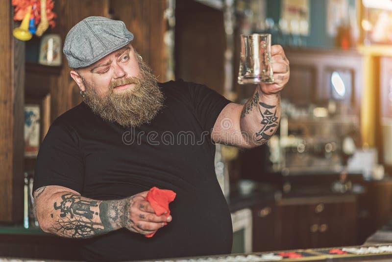 Gruby barman wyciera piwnego szkło należnie obrazy stock