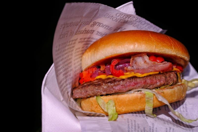 Gruby hamburger w papierowym opakowaniu przy czernią zdjęcia stock