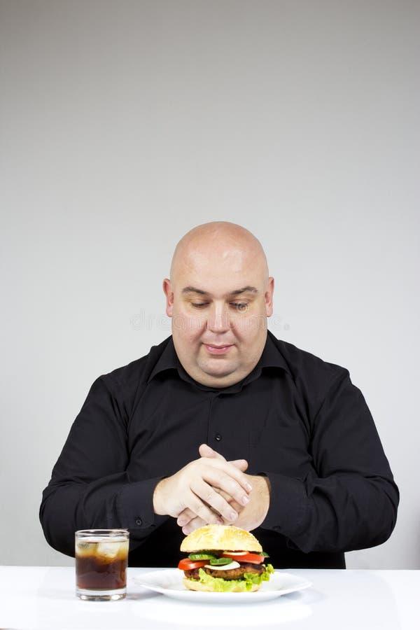 Gruby mężczyzna łasowania hamburger zdjęcia royalty free