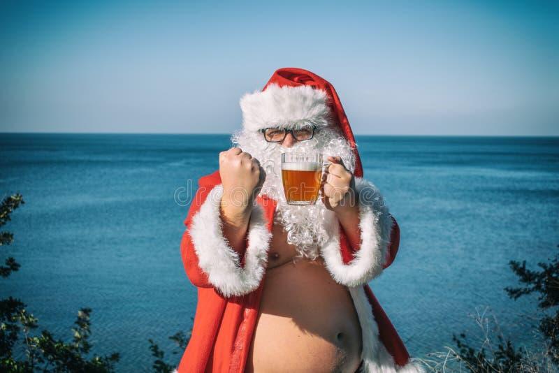Gruby mężczyzna pije piwo na oceanie w szkłach ubierał jako Santa Śmieszny, pijący i szczęśliwy obrazy stock