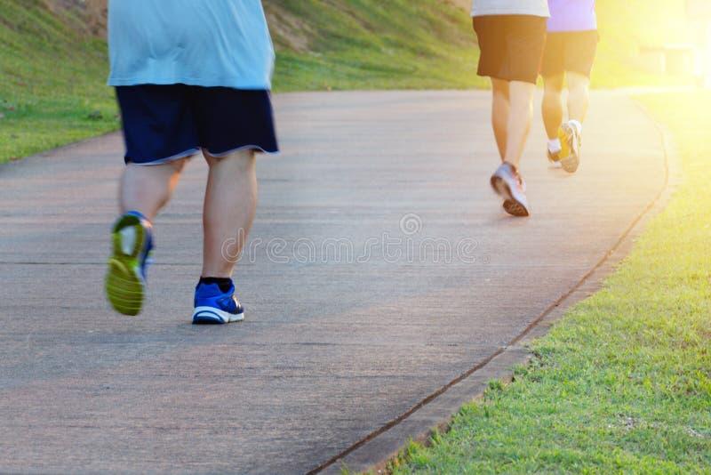 Gruby mężczyzny jogging, łapie w górę cienkich mężczyzn z Sprawność fizyczna i zdrowy styl życia, plenerowego sporta aktywność obraz royalty free
