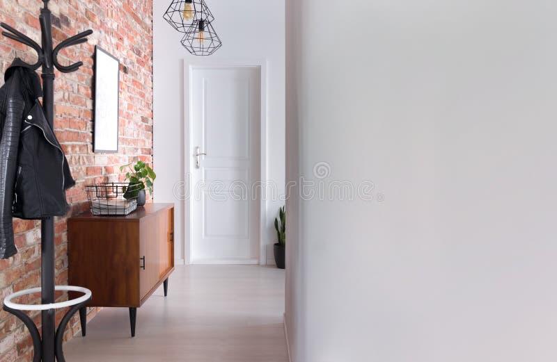 Gruccia per vestiti del corridoio dell'appartamento, armadietto e muro di mattoni alla moda, foto reale fotografia stock