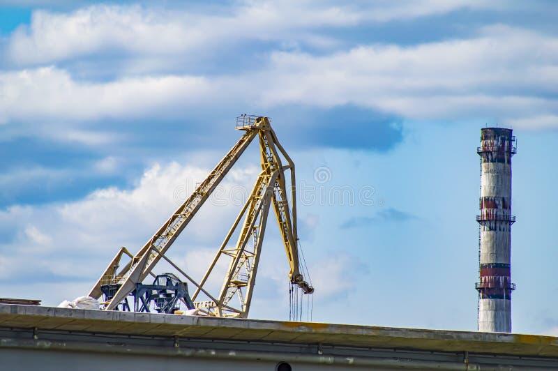 Grue à quai et cheminée industrielle contre un ciel bleu nuageux photos stock