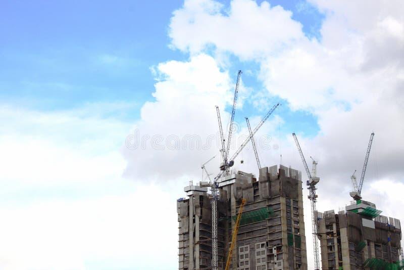 Grue à tour ayant beaucoup d'étages et nouvelle maison urbaine résidentielle non finie en construction, vue de face de bâtiments  image stock
