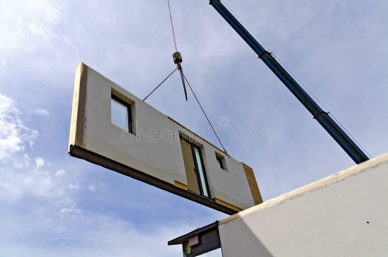 Grue avec une partie d'une maison préfabriquée images libres de droits