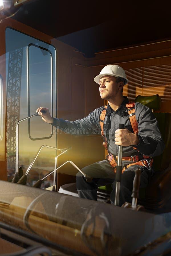 Grue d'opérateur d'ingénieur dans l'action Il reposent un dessus dans la cabine et le travail de grue photos libres de droits