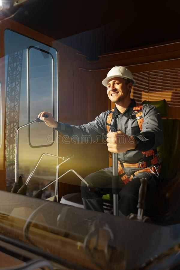 Grue d'opérateur d'ingénieur dans l'action Il reposent un dessus dans la cabine et le travail de grue photographie stock libre de droits