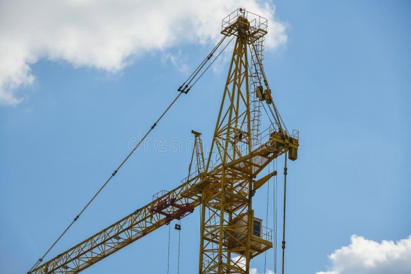 Grue de construction ayant beaucoup d'étages avec une longue flèche de couleur jaune contre le ciel bleu au-dessus d'un nouveau b photos stock