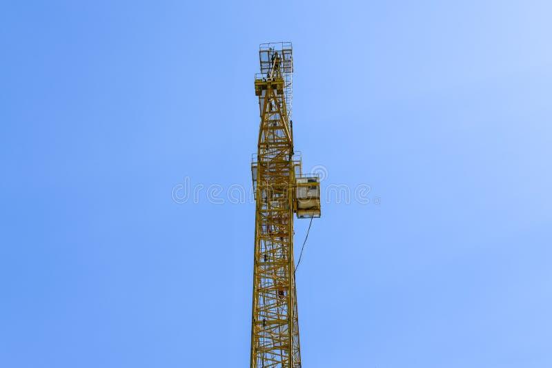 Grue de construction ayant beaucoup d'étages avec une longue flèche de couleur jaune contre le ciel bleu au-dessus d'un nouveau b photo stock