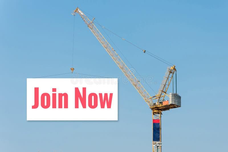 Grue de construction industrielle tenant un panneau d'affichage photo libre de droits
