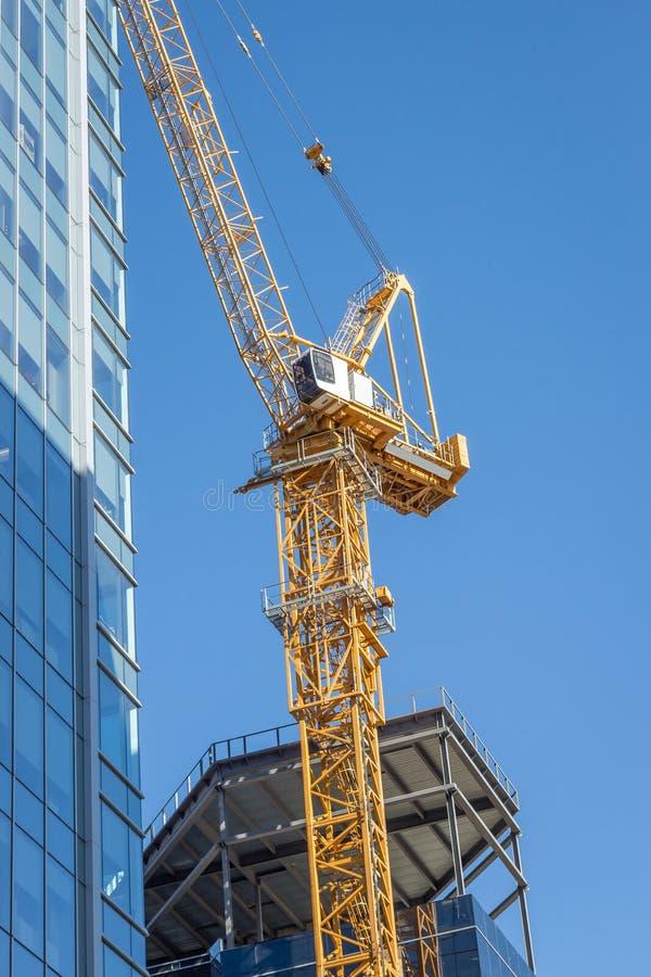 Grue de construction très grande à côté de gratte-ciel images stock