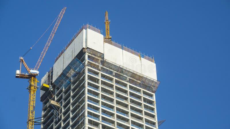 Grue et site de construction de bâtiments contre le ciel bleu image libre de droits