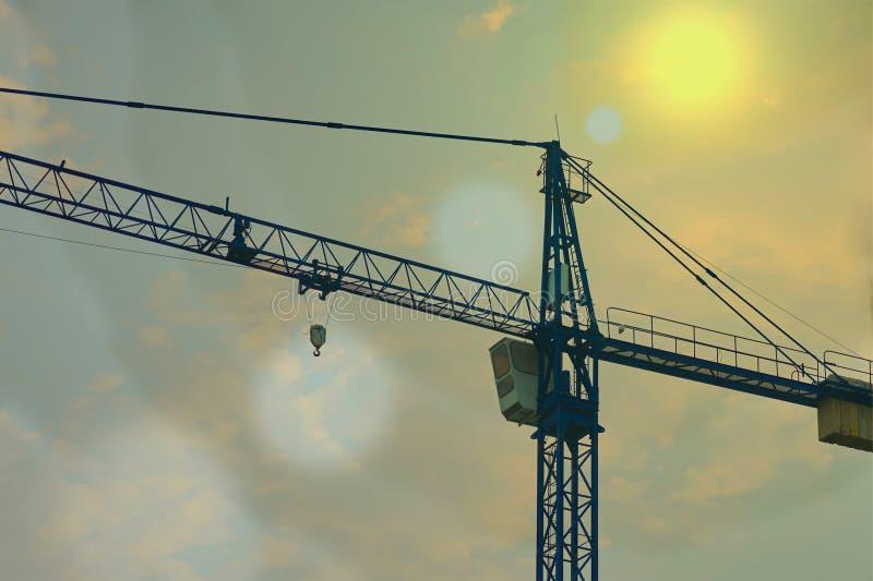 Grue fonctionnant dans le secteur de construction avec la fusée du soleil photo libre de droits