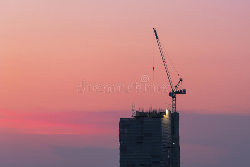 Grue industrielle au chantier de construction avec le ciel de coucher du soleil photos libres de droits