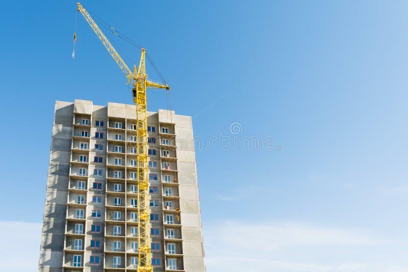 Grue ? tour jaune et la construction d'un b?timent ? plusiers ?tages contre un ciel bleu photos libres de droits