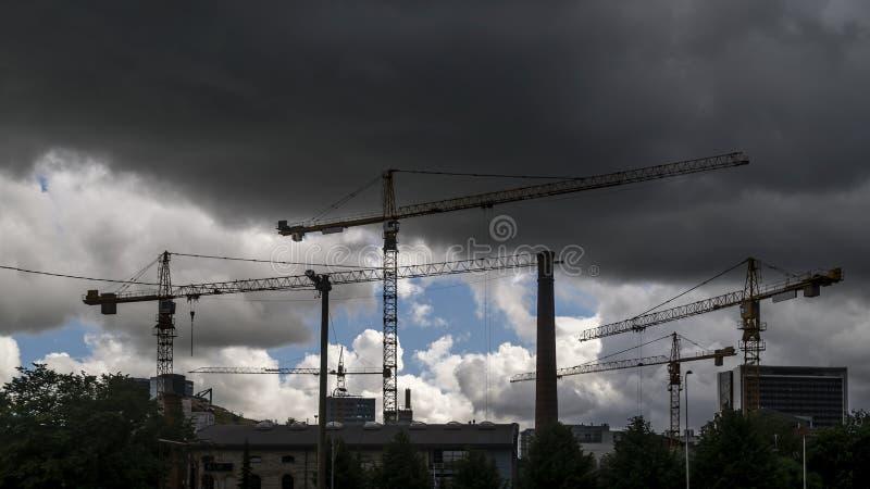 Grues à tour au travail sous l'orage dans un secteur en construction dans la banlieue de la ville de Tallinn, Estonie photo stock