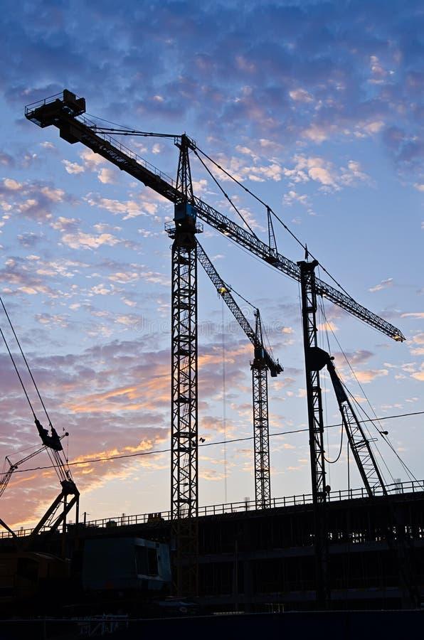 Grues à tour en silhouette sur le chantier de construction images libres de droits