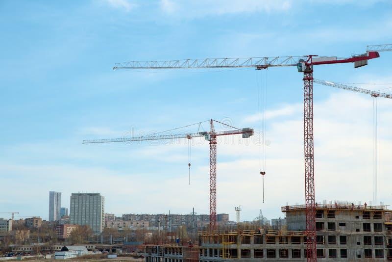 Grues de bâtiment et bâtiment en construction contre le ciel nuageux photo libre de droits