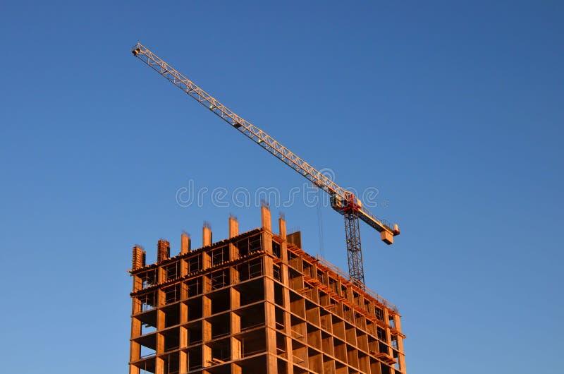 grues de construction et silhouettes de bâtiment au-dessus du soleil au lever de soleil Fond industriel abstrait de ciel bleu et photographie stock libre de droits