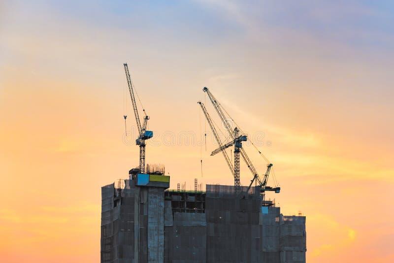 Grues de construction industrielles au chantier de construction avec le coucher du soleil photographie stock