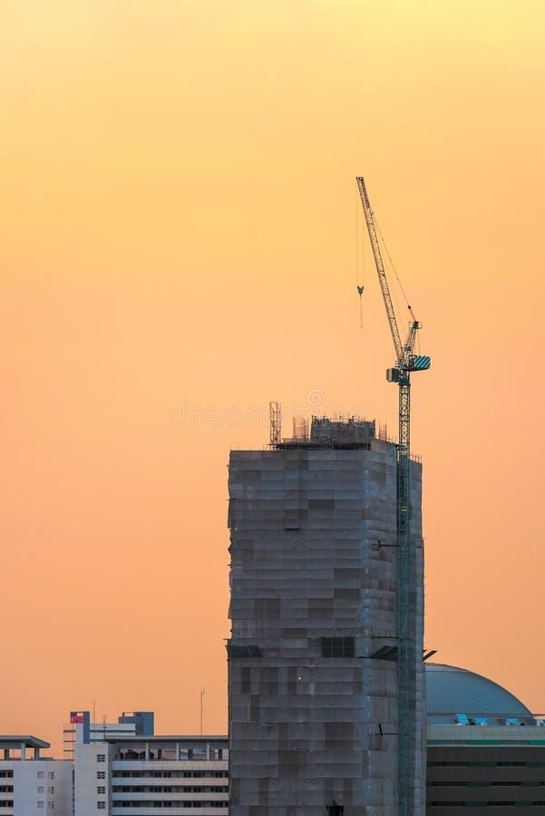 Grues de construction industrielles au chantier de construction avec le coucher du soleil photo libre de droits