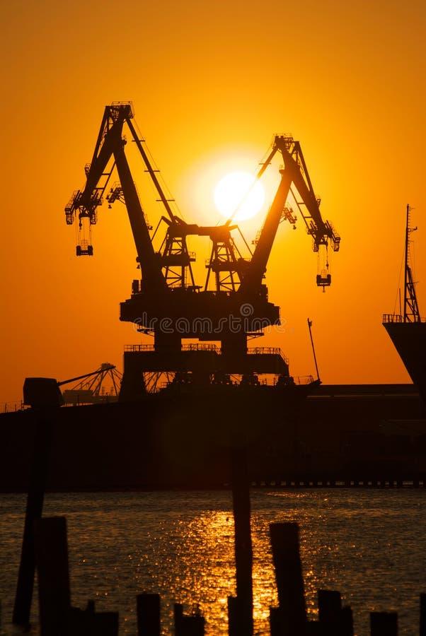 Grues industrielles au coucher du soleil photos libres de droits