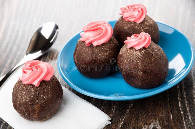 Grula zasycha z różową śmietanką w spodeczku, teaspoon, tort na tkance na drewnianym stole fotografia stock