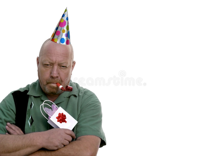 Grumpy Birthday Man. Man with grumpy expression with birthday hat, gift and party favor stock image