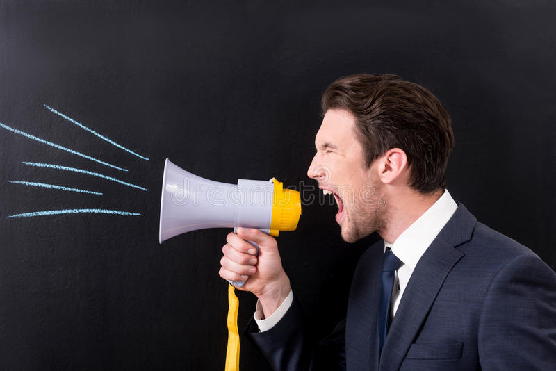 Grumpy businessman is yelling through bullhorn. Aggressive management concept. Angry young man is screaming through megaphone while standing against dark royalty free stock photo