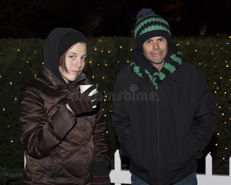 Grumpy father and daughter standing in the cold in front of bushes with Christmas lights stock photography