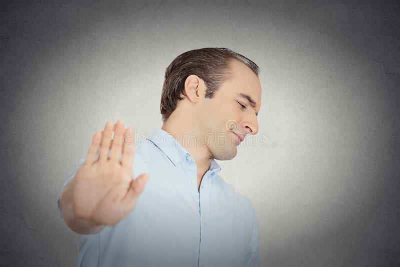 Grumpy man with bad attitude giving talk to hand gesture. Closeup portrait young handsome grumpy man with bad attitude giving talk to hand gesture with palm royalty free stock photos