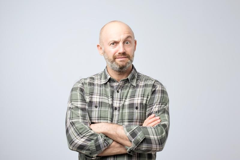 Grumpy mature european man posing in studio with arms folded, feeling insulted while having quarrel with his girlfriend royalty free stock photo