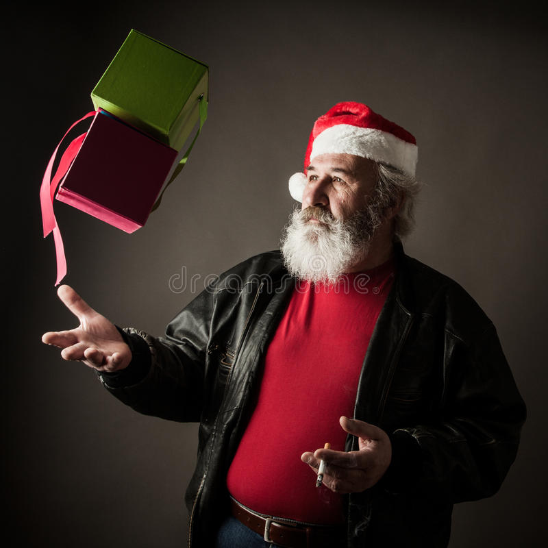 Grumpy Santa Claus. With gift boxes and cigarette royalty free stock photo
