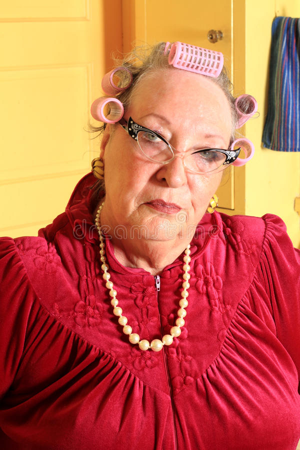 Grumpy Senior Granny with Curlers. Silly Portrait of a grumpy senior gray haired granny lady wearing cat eye glasses, pearls and curlers in her hair in an old stock photography