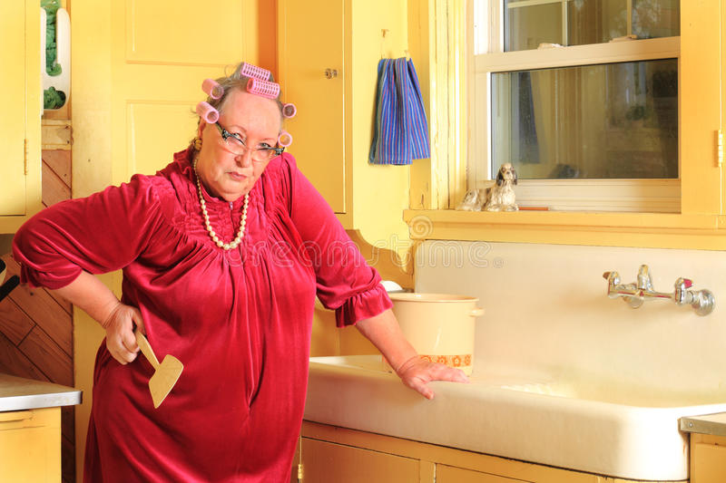 Grumpy Senior Lady Holding Fly Swatter. Silly Portrait of a grumpy senior gray haired lady wearing cat eye glasses, pearls and curlers in her hair in an old royalty free stock photo