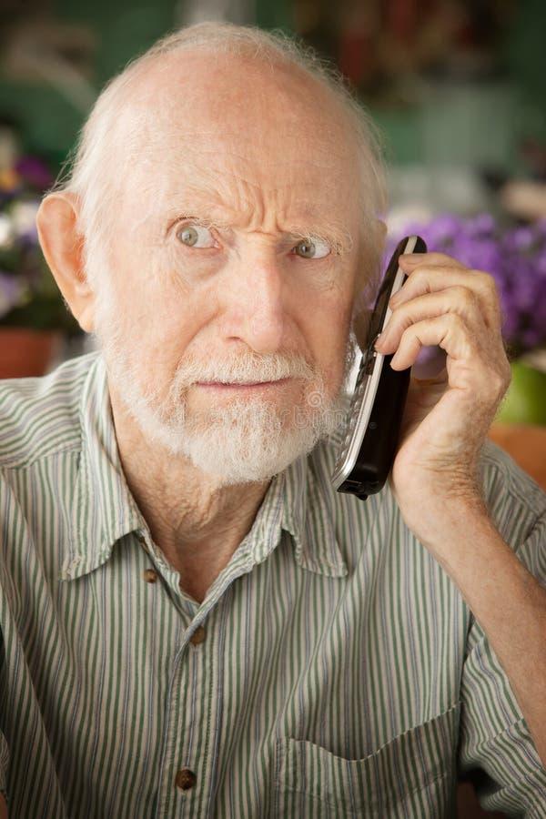 Grumpy senior man on telephone stock photos