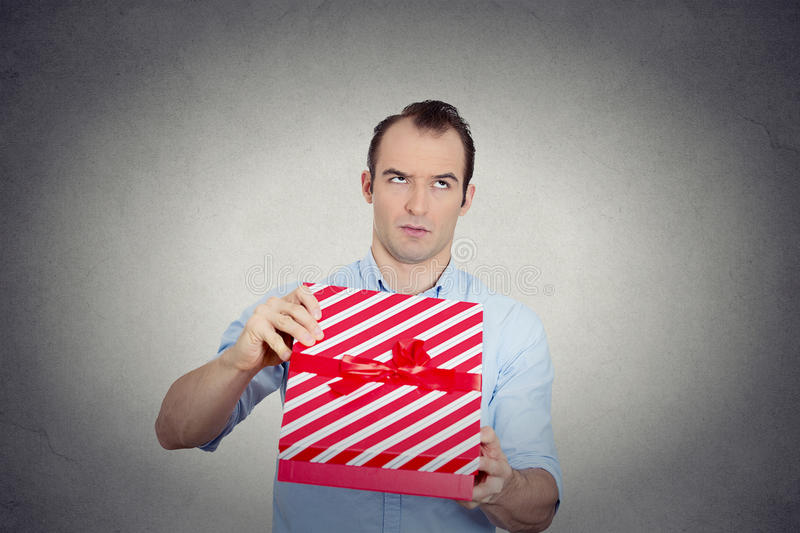 Grumpy unhappy upset man holding red gift box very displeased stock photo