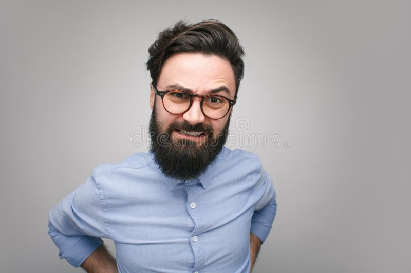 Grumpy young man in glasses stock images