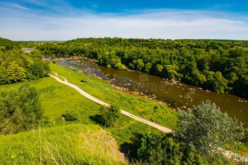 Grund bergflod som flödar längs grönt bergigt område arkivbilder