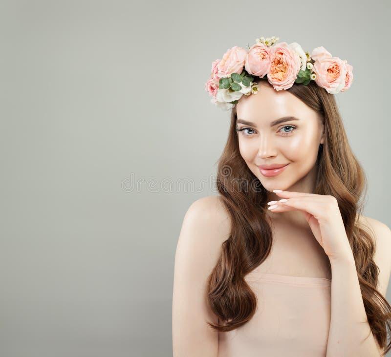 grund kvinna f?r gladlynt djupf?ltst?ende Ung modell med klar hud, långt sunt lockigt hår och blommor Skincare och ansikts- behan arkivbild