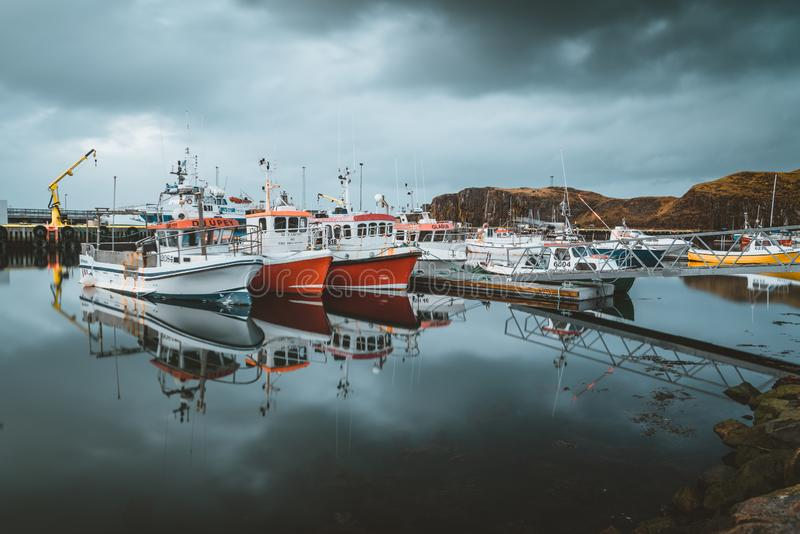Grundarfjordur, Iceland - 03 January 2019: Harbor with motionless boats during the twilight of the afternoon, Kirkjufell royalty free stock photos