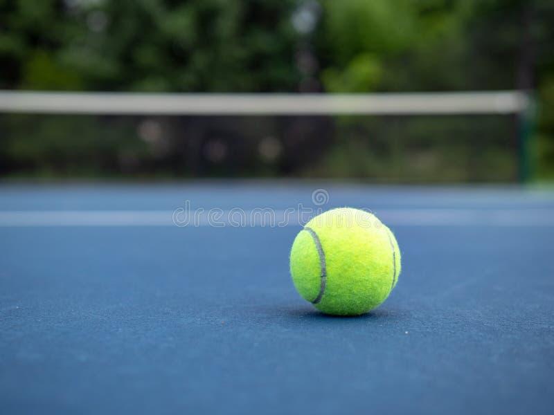 Grundat sammanträde för tennisboll på jordning med domstolen som är netto i bakgrund royaltyfri foto