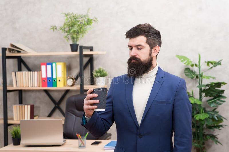 Grundkaffee verbessert Bürokultur Managergeschäftsmannunternehmer-Grifftasse kaffee des Mannes bärtiger Entspannter Manager lizenzfreies stockfoto