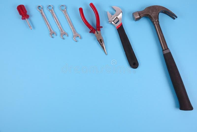 Grundläggande hjälpmedel som hammaren och skiftnycklar på en blå bakgrund arkivbild