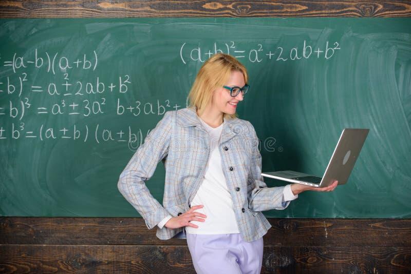 Grundl?ggande skolutbildning Elegant dam f?r l?rare med den moderna b?rbara datorn som surfar svart tavlabakgrund f?r internet av arkivfoton
