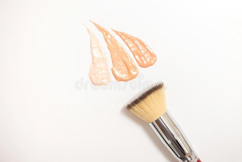 Grundlagencremetropfen und Abstriche von verschiedenen Schatten für verschiedene Hautarten mit Bürsten für Anwendung und Schattie lizenzfreie stockfotografie