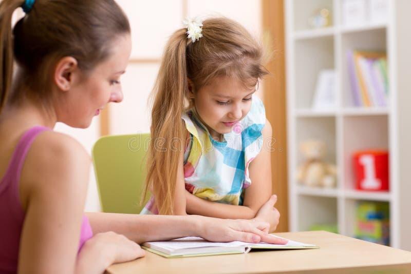 Grundlegende Schüler-Lesung mit Lehrer stockfotografie