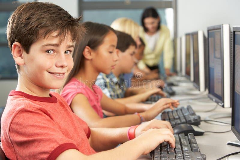 Grundlegende Studenten, die an den Computern im Klassenzimmer arbeiten stockbild