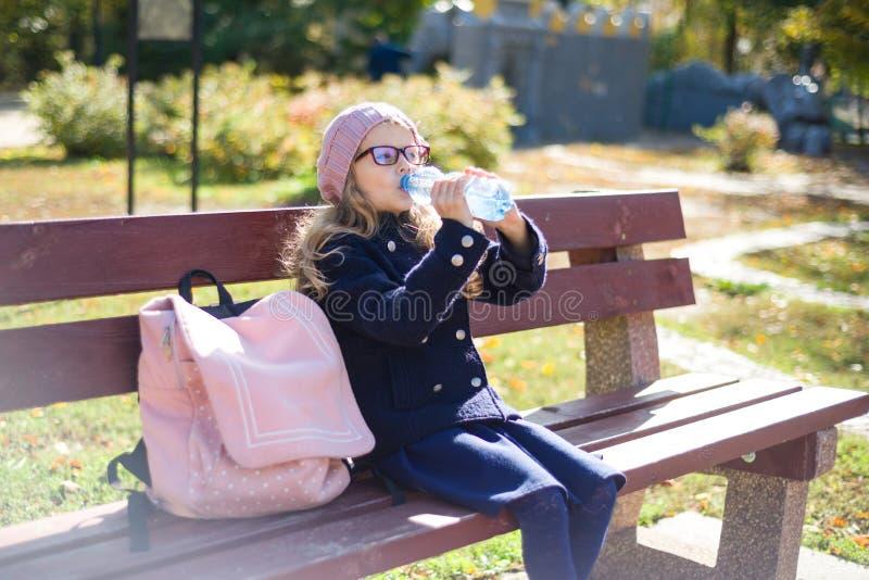 Grundschüler des kleinen Mädchens, der auf Bank mit Rucksack, Trinkwasser von der Flasche sitzt Hintergrundherbst-Stadtpark stockbild